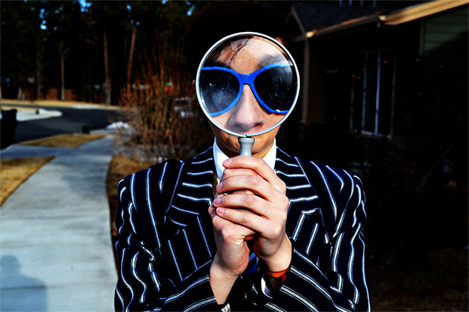 man with magnifying glass and funny jacket